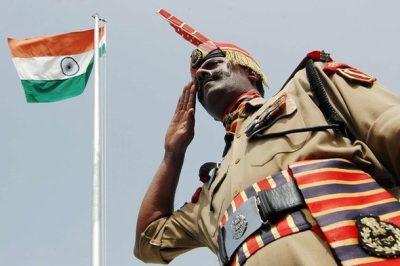 Индийский военнослужащий на фоне государственного флага