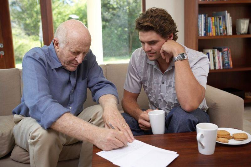 Пожилой мужчина подписывает документ